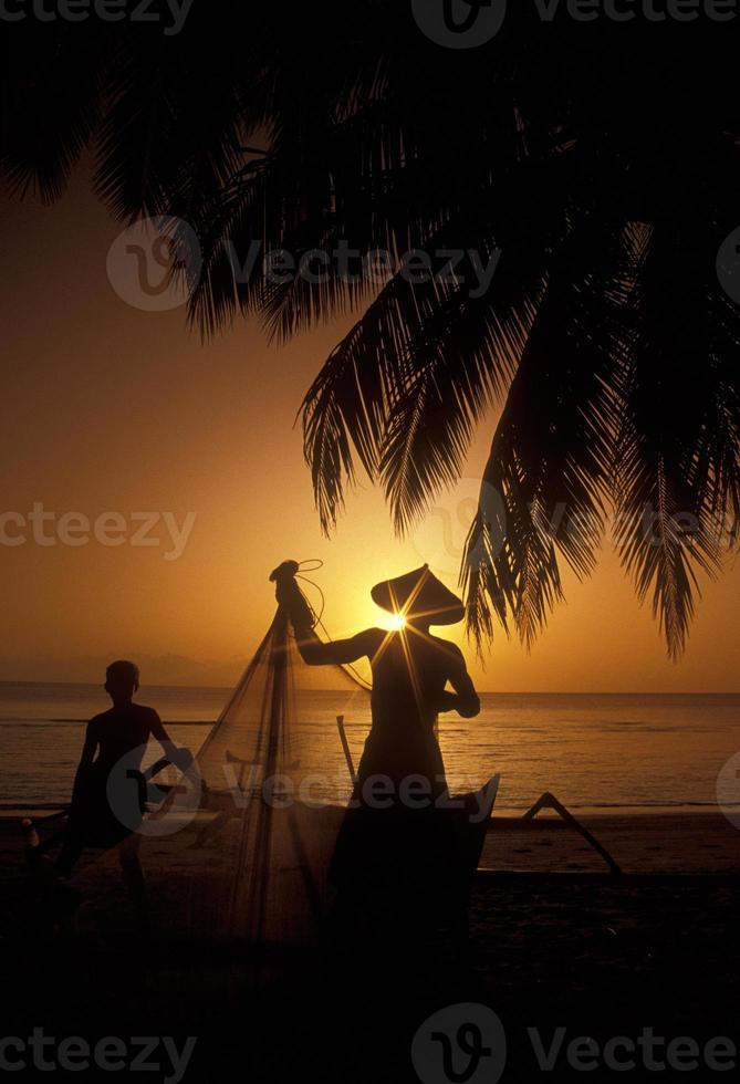 Fishermen Silhouettes, Indonesia, on Tropical Beach at Sunset photo