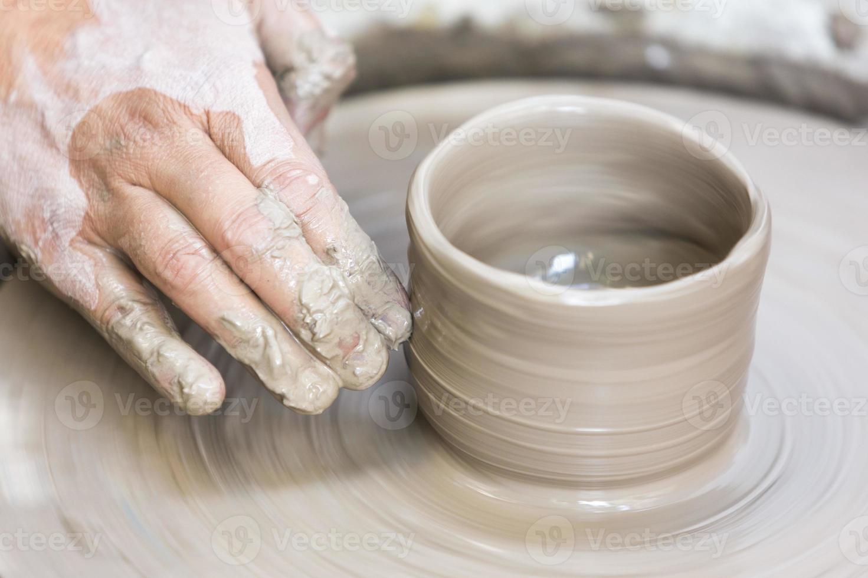 haciendo una taza de cerámica en el volante foto