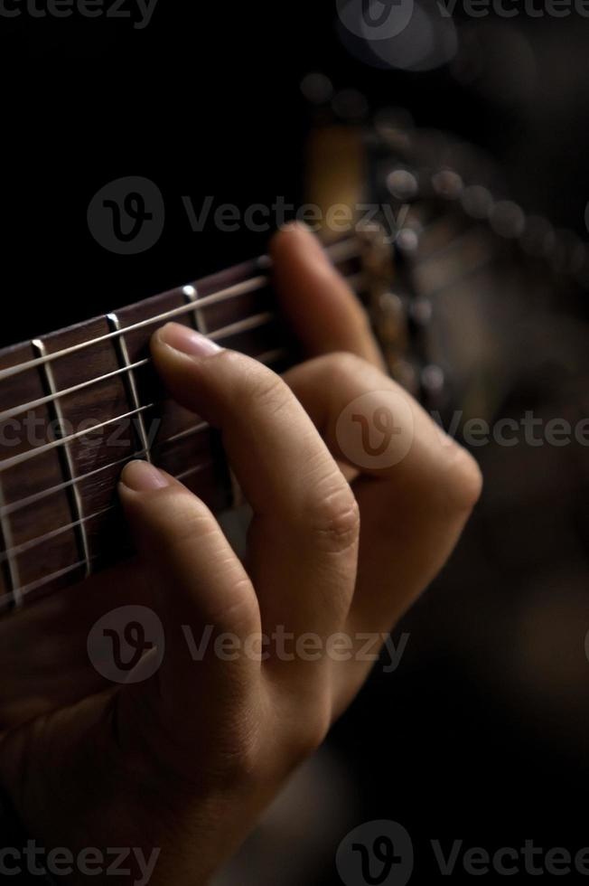 The hand of man playing guitar photo
