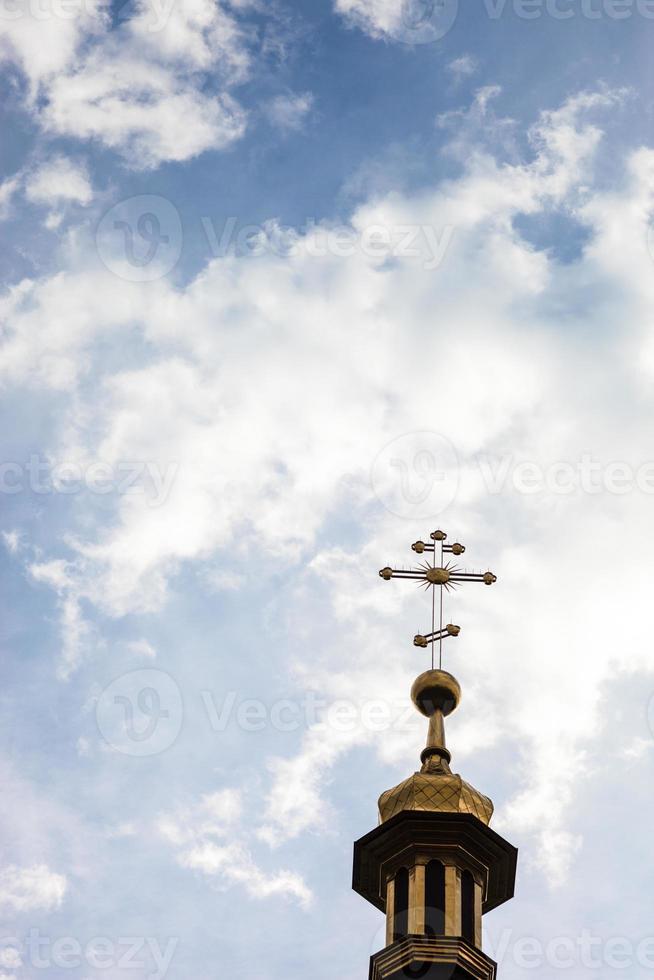 Cross of the orthodox Christian church against the cloudy sky photo