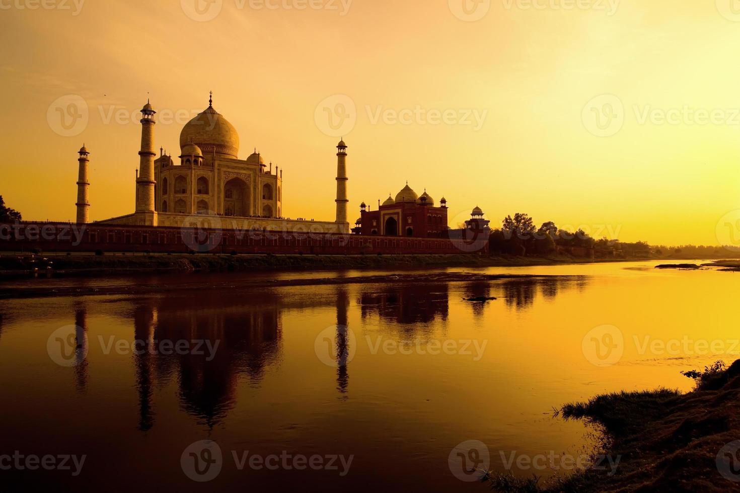 Taj Mahal at sunset refected in the Yamuna river. photo