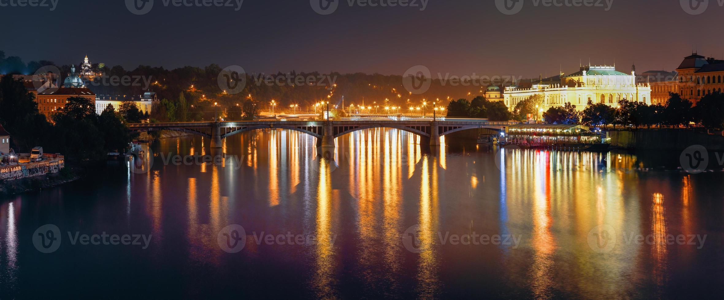 vista panorámica nocturna del río vltava y el puente de manes foto