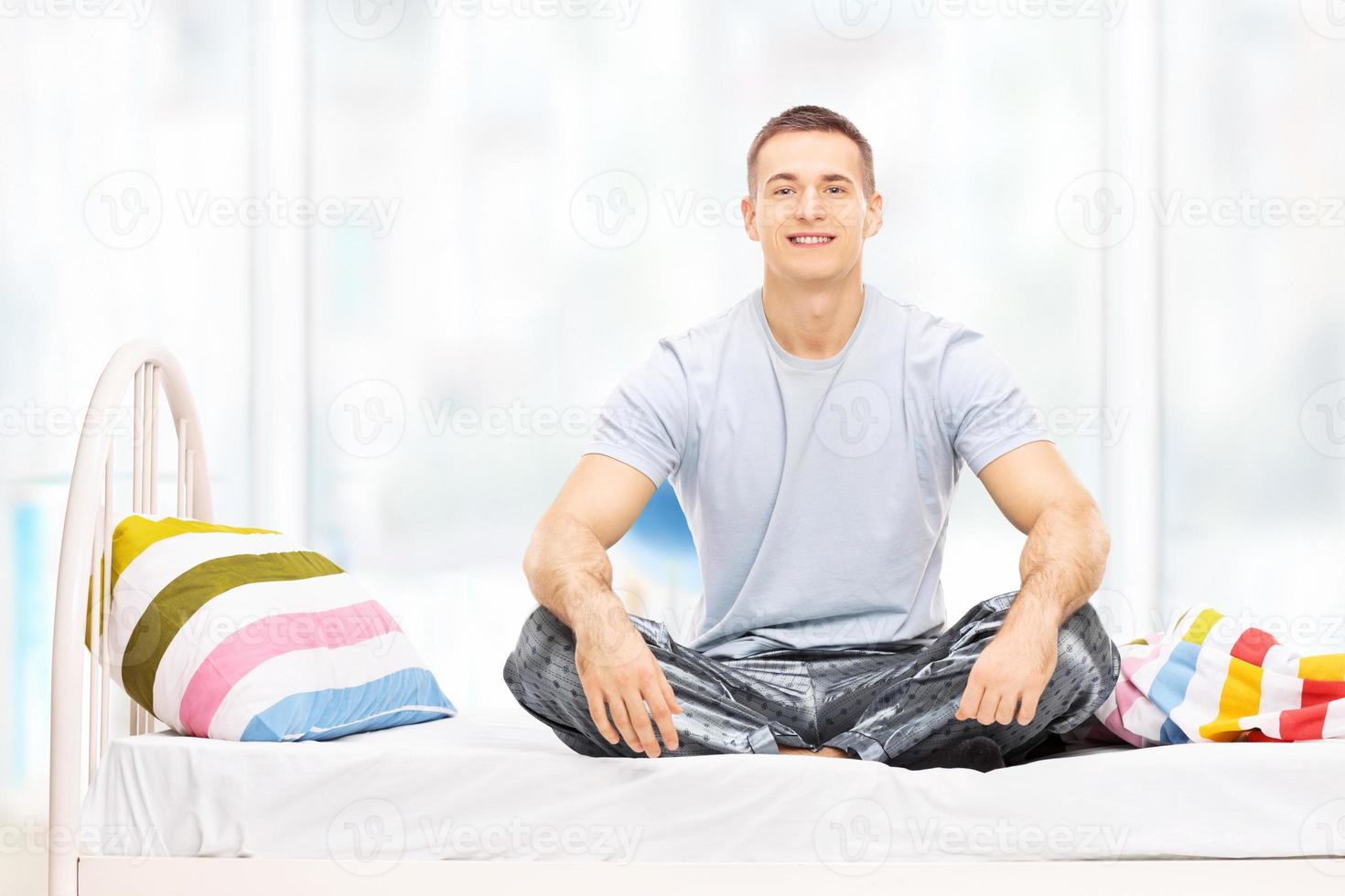 Young man in pajamas sitting on a bed photo