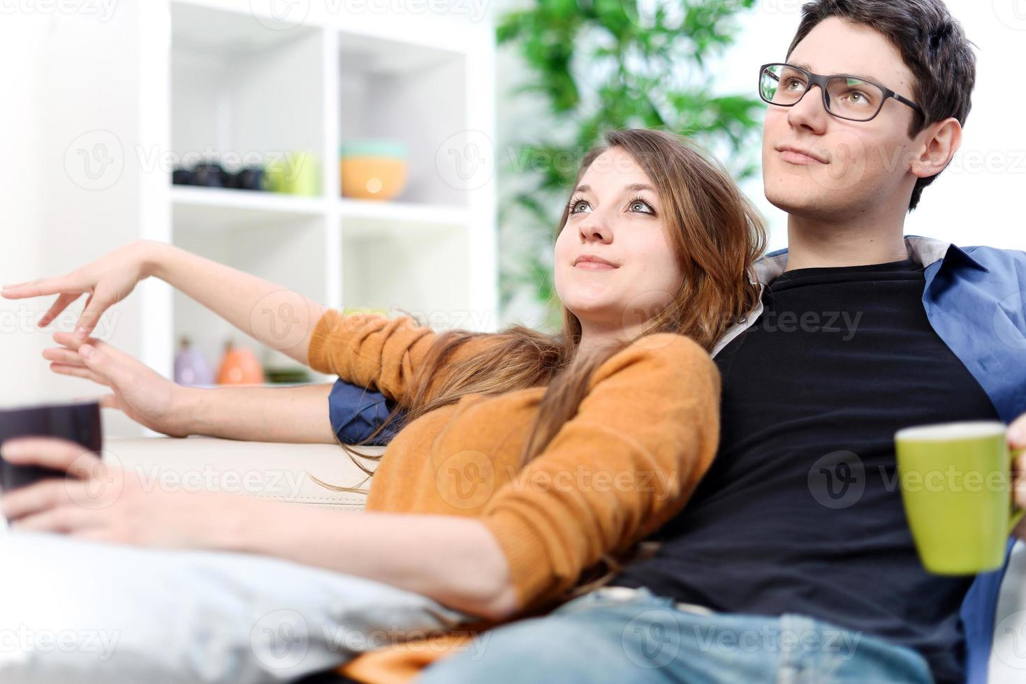 encantadora pareja viendo televisión mientras bebe té en la sala de estar foto
