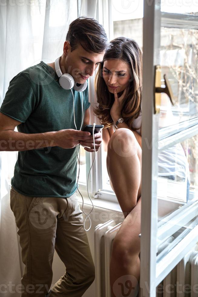 Couple standing by the window and listnening to music photo