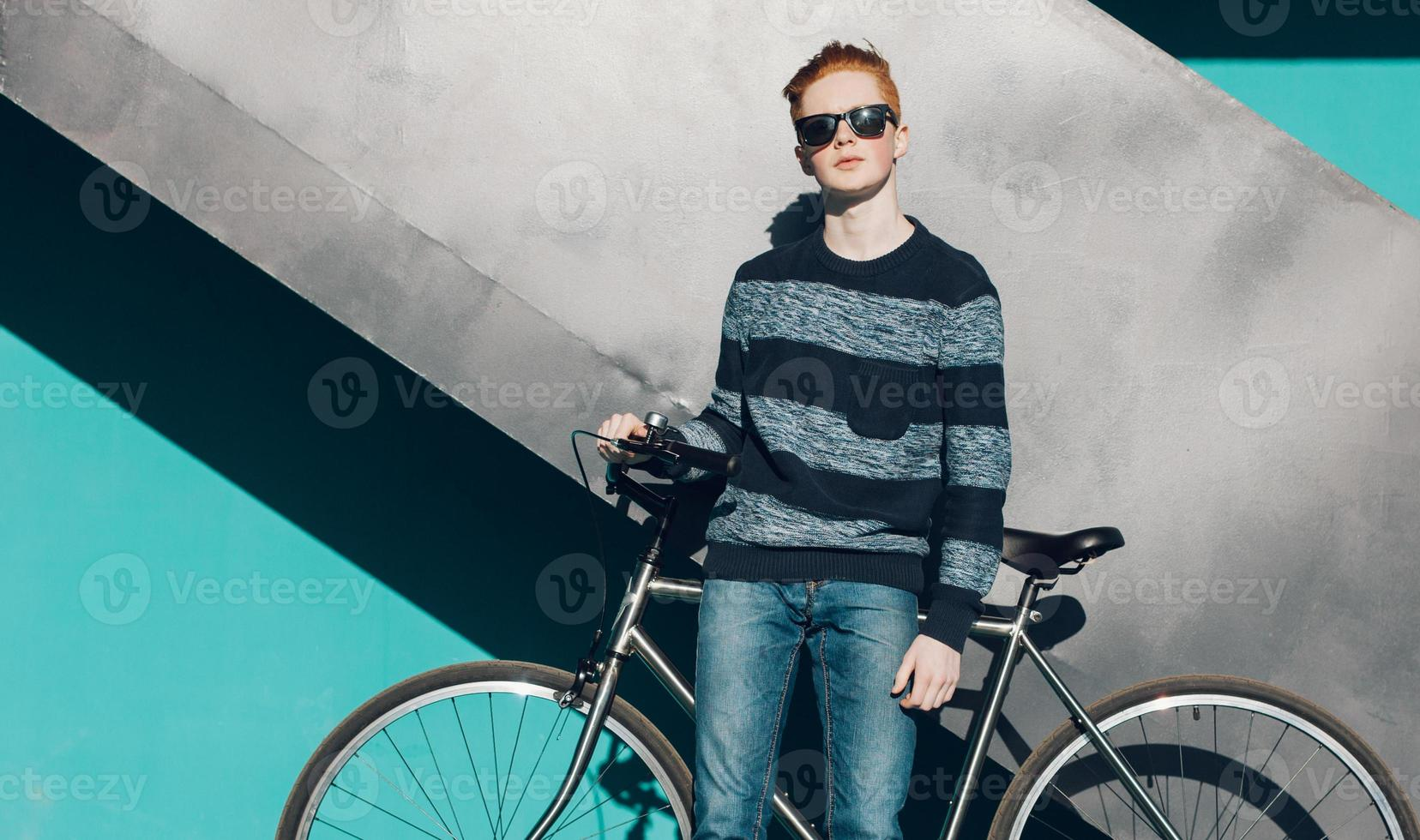 Young redhead man standing next to a vintage bicycle photo