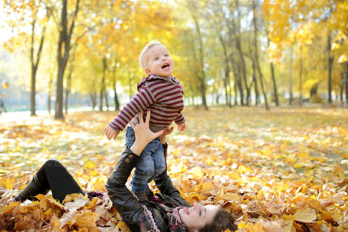 madre y el niño caminan en el parque otoño foto