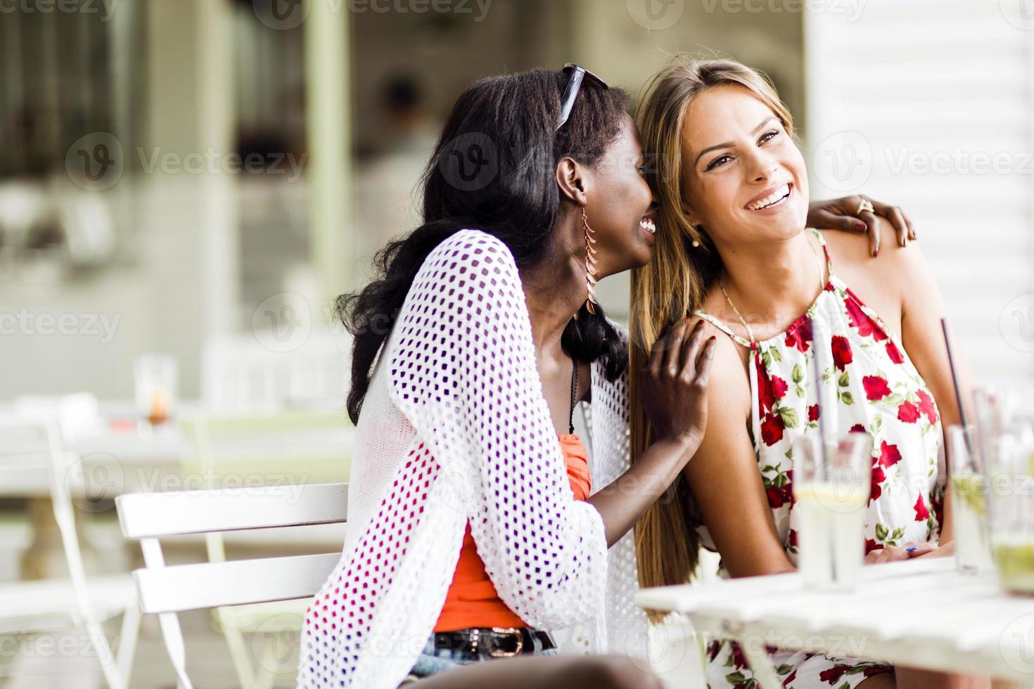 Dos mujeres atractivas cotilleando y susurrando al aire libre en un café foto