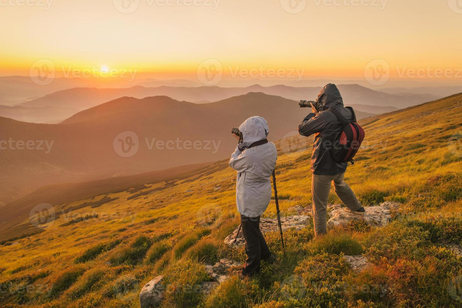 Photographers takes a sunset in the mountains photo