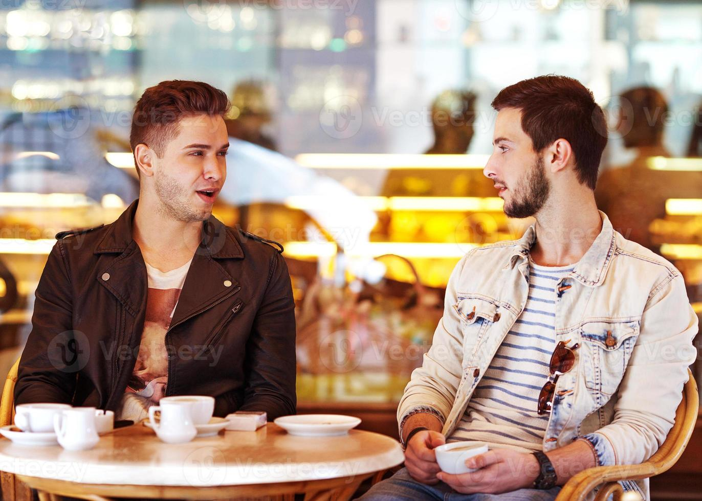 Two young men / students using tablet computer in cafe photo