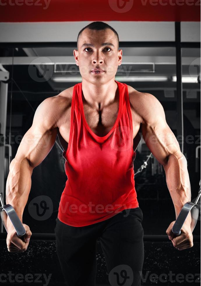 bodybuilder pumping up muscles on crossover photo