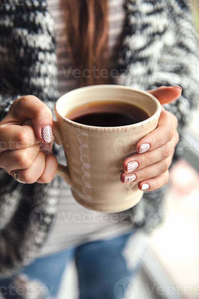 Girl's hands holding cup of coffee photo