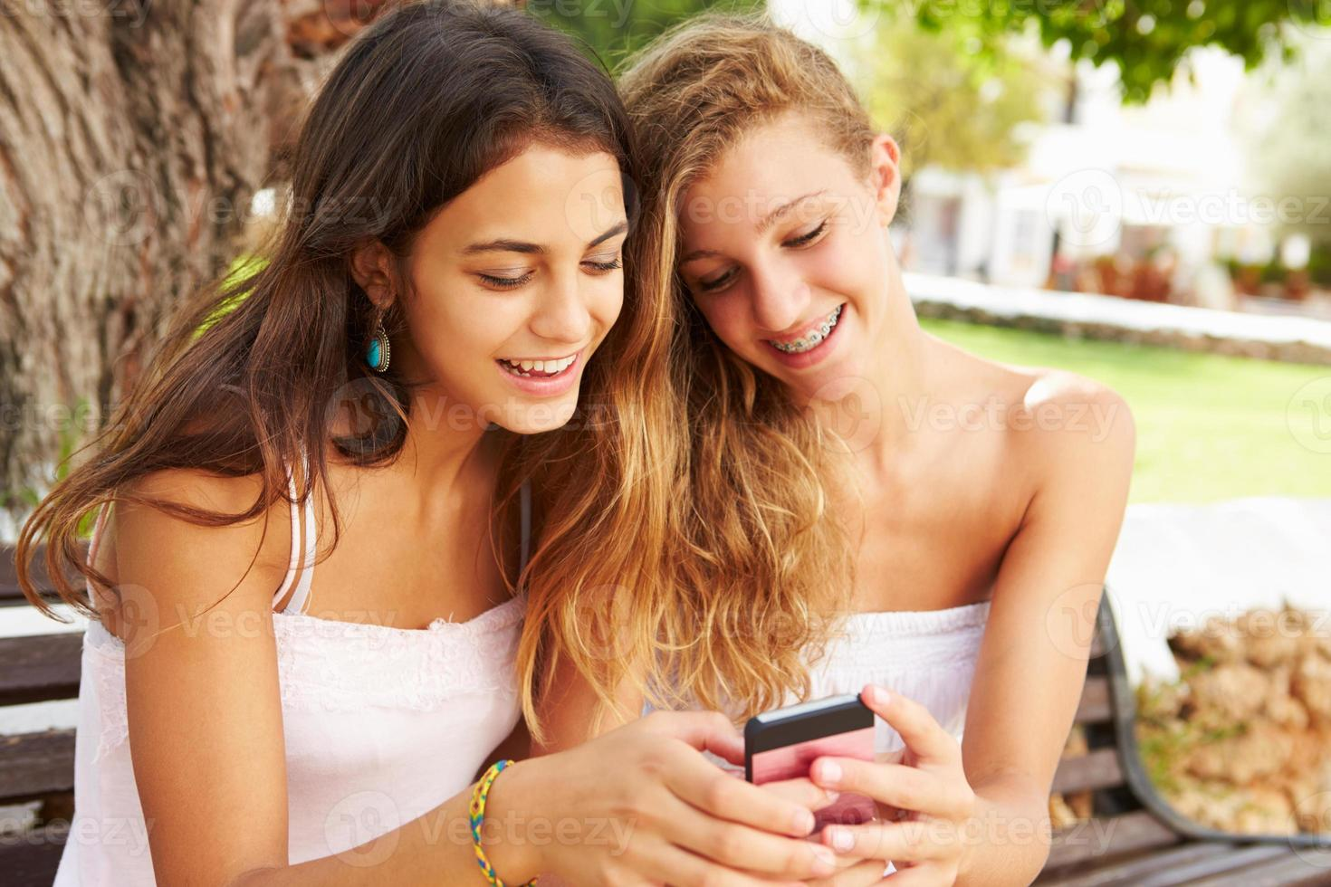 Dos chicas adolescentes que usan el teléfono móvil sentado en el banco del parque foto