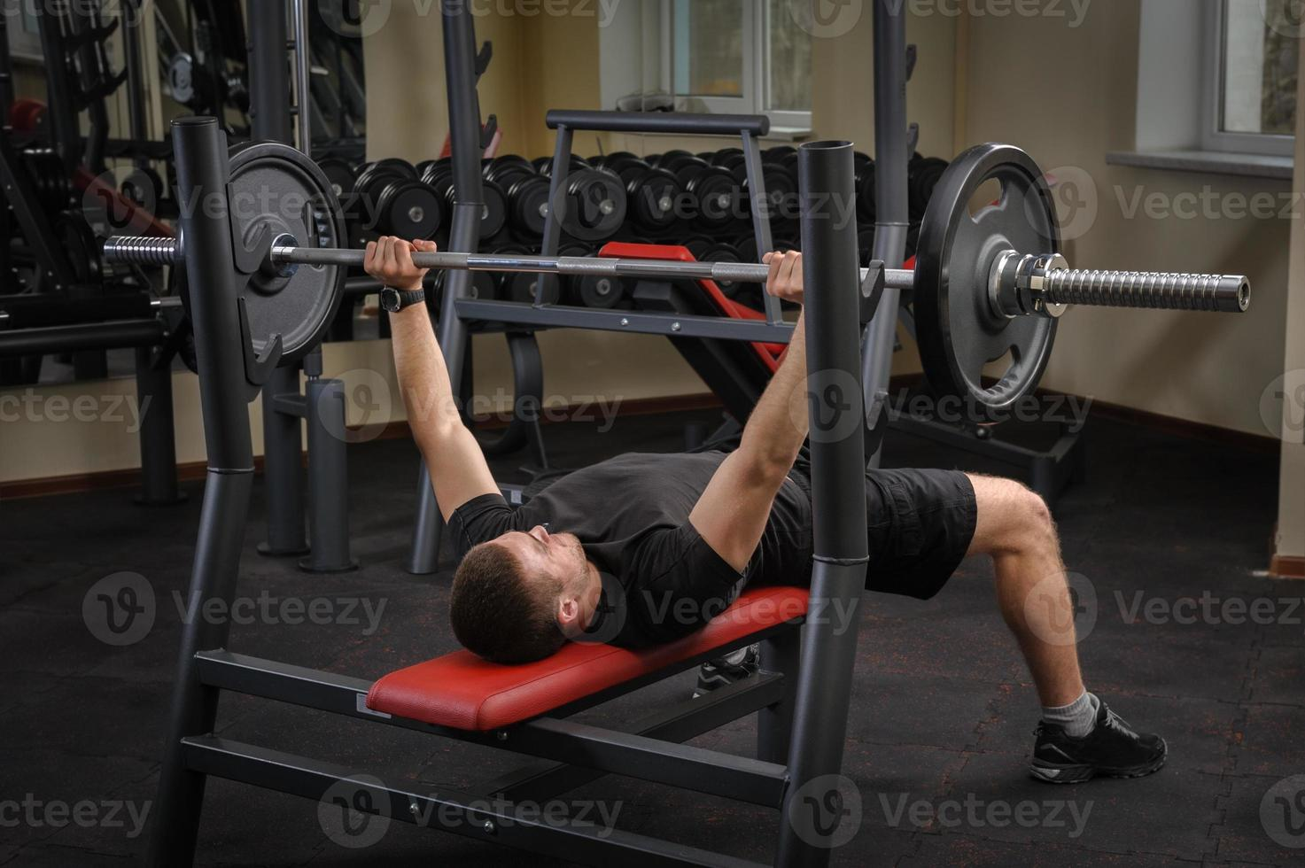 young man doing bench press workout in gym photo