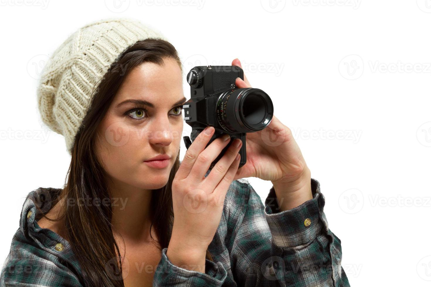 Young woman with brown hair holds camera photo
