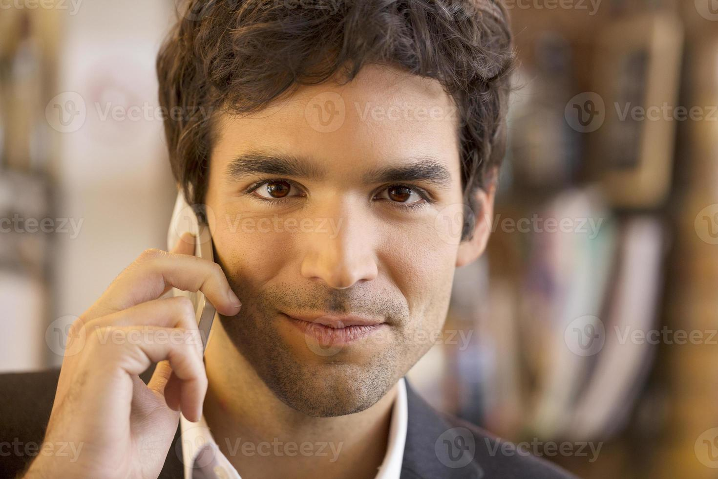 Handsome man calling with a cell phone in coffee bar photo