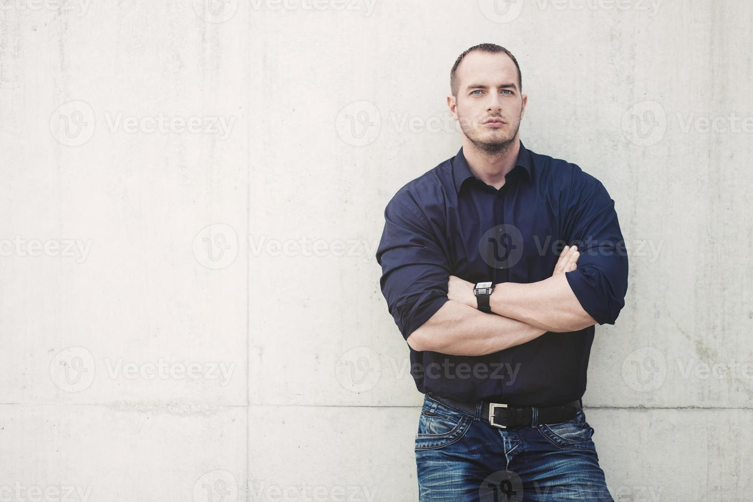 Man posing outside, leaning on concrete wall photo