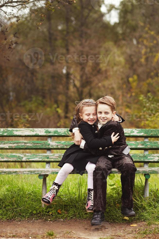 Brother and sister kids hugging on a bench photo