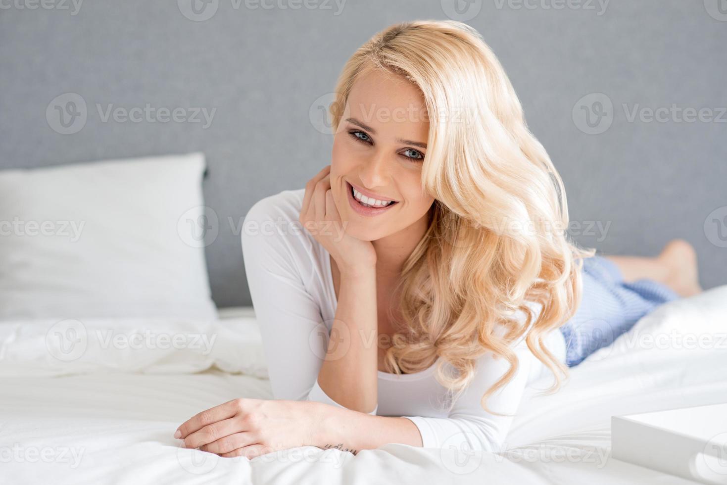 hermosa mujer rubia acostada en su cama foto
