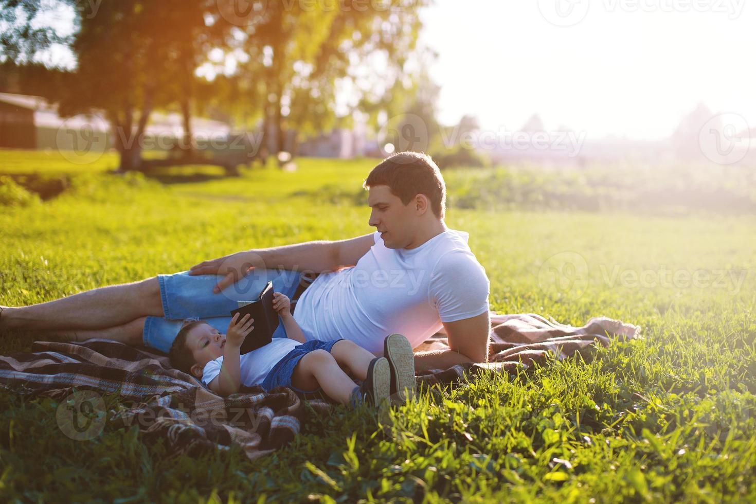 padre e hijo descansando en el parque en el césped foto