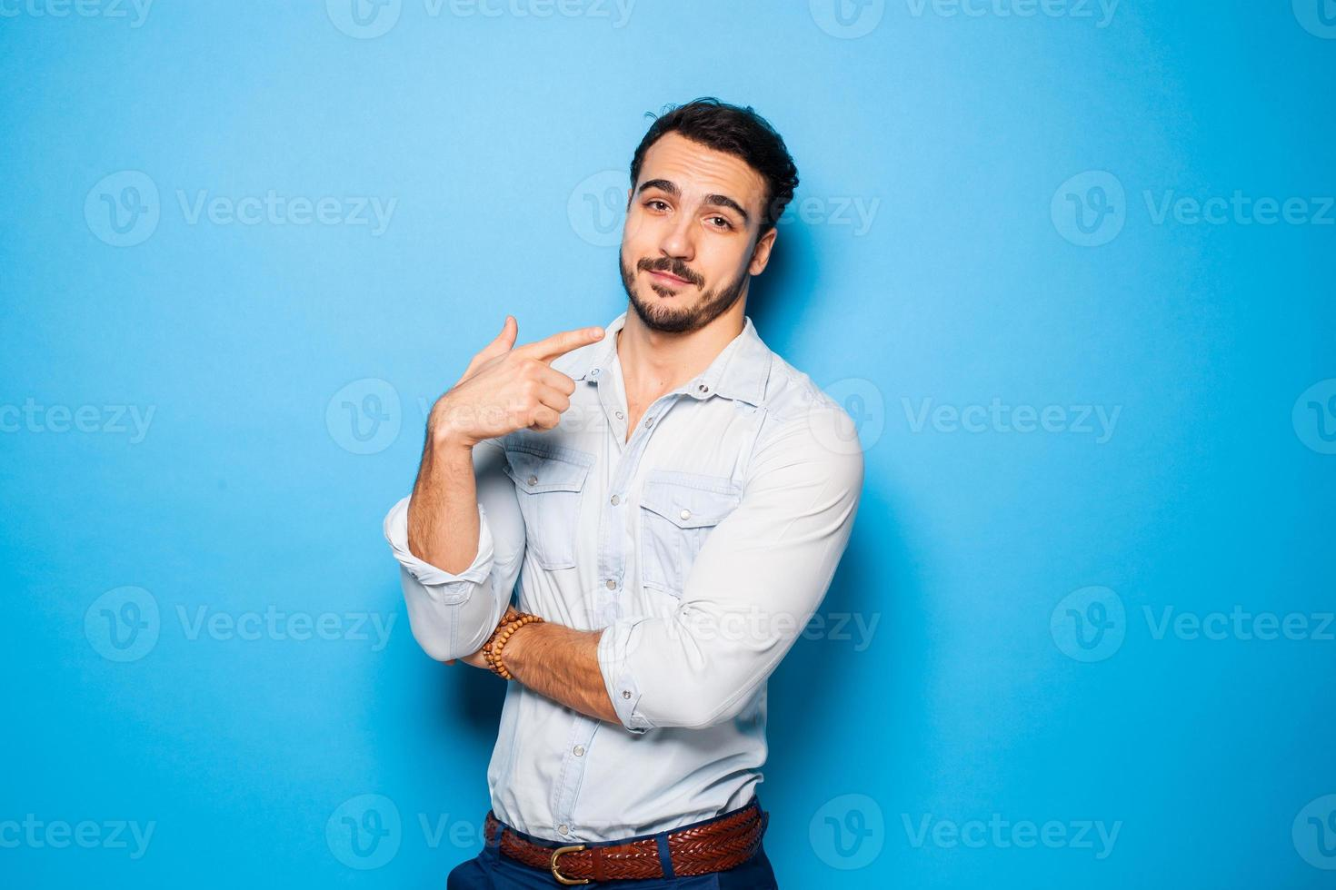 Handsome adult and masculine man on a blue background photo