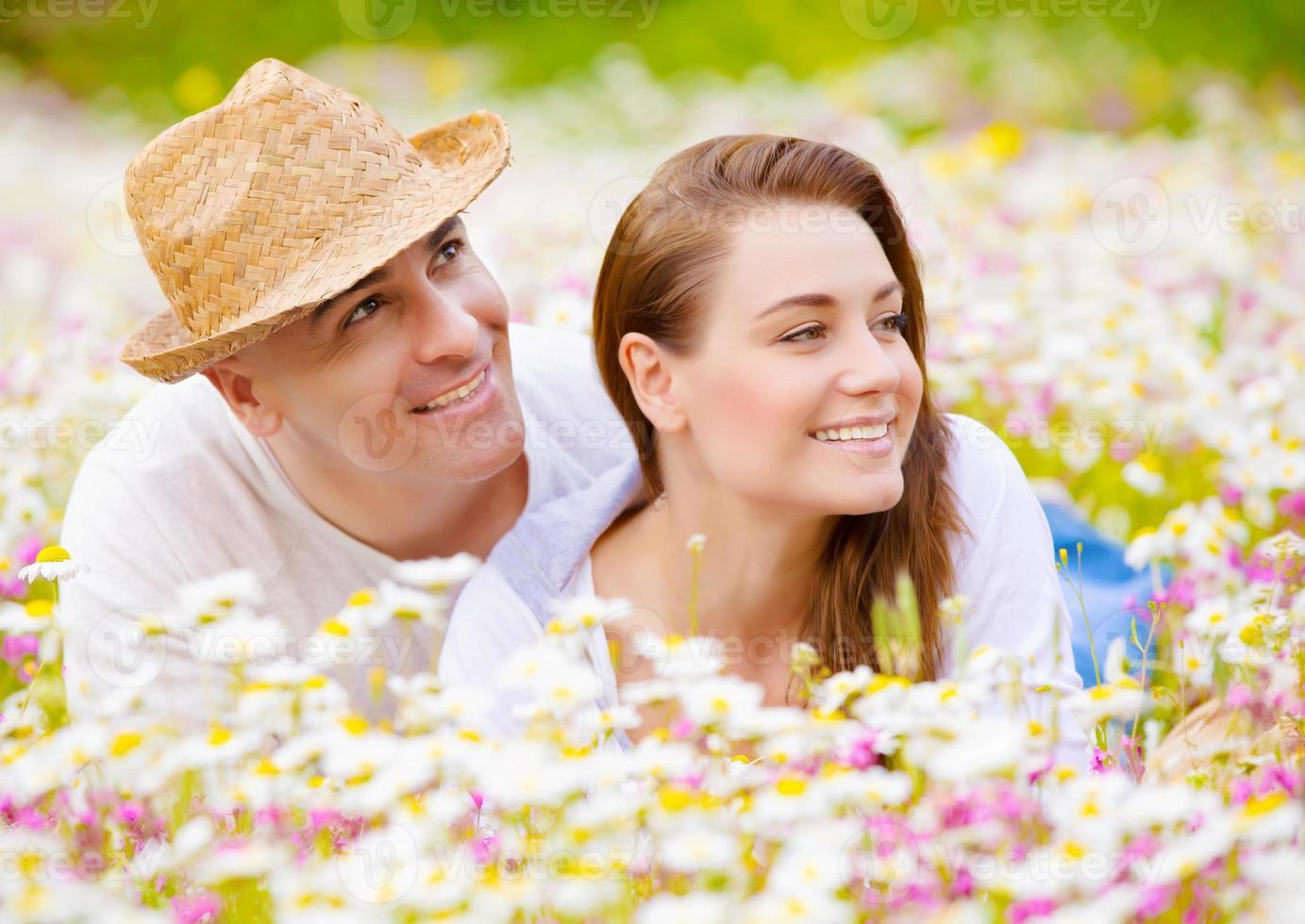 hermosa pareja en prado de manzanilla foto