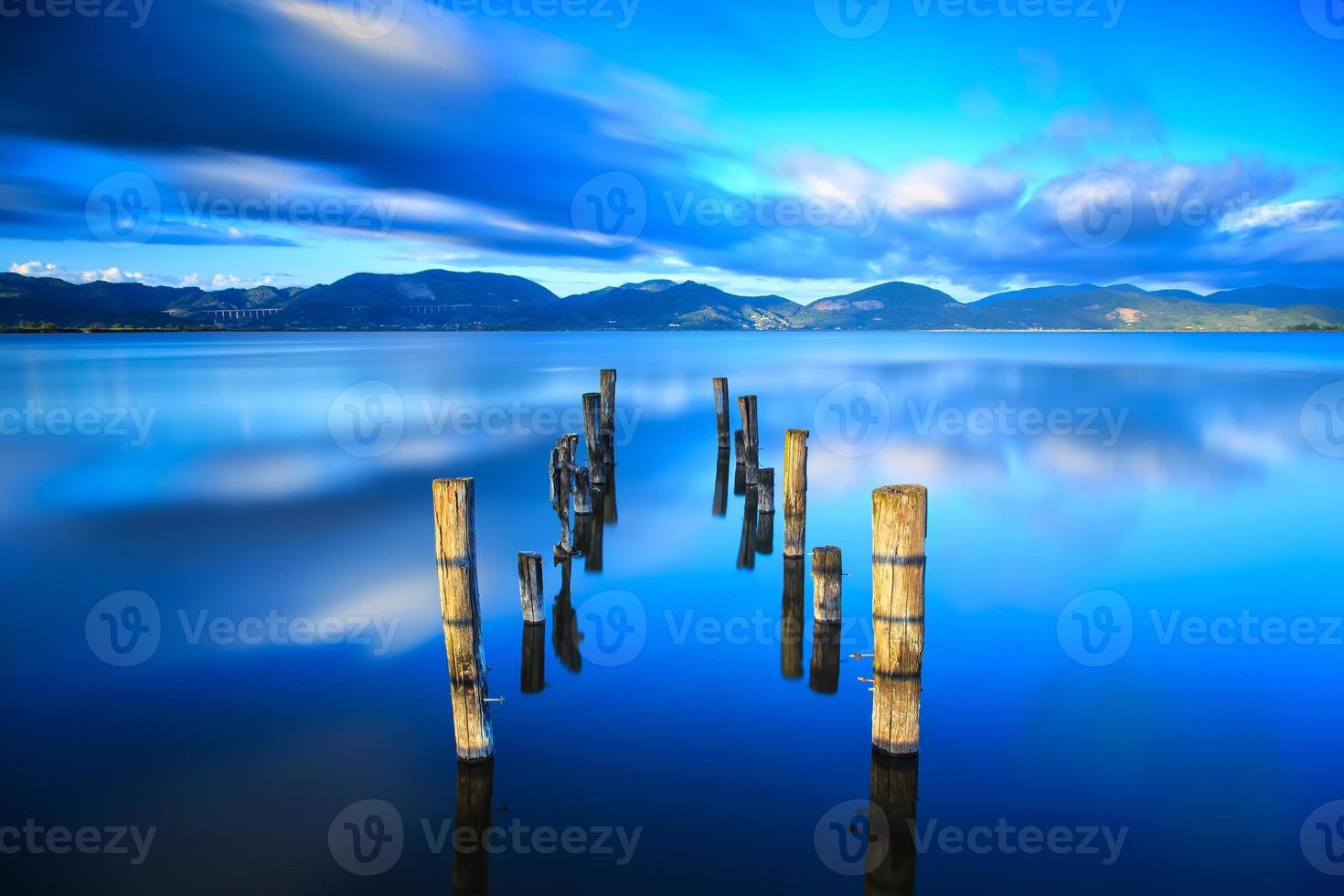 muelle de madera, embarcadero permanece en un lago azul puesta de sol, cielo foto