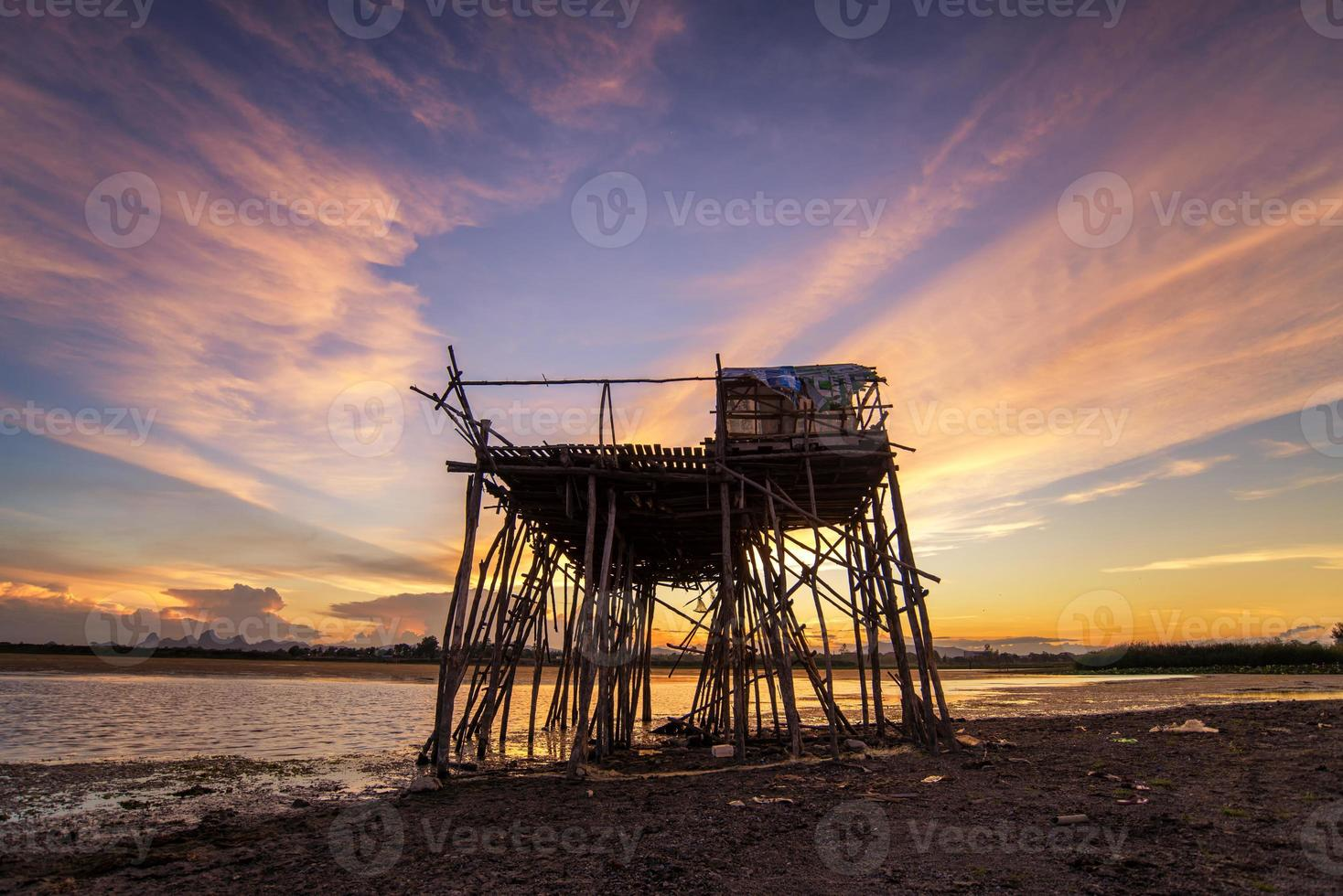 Abandon wooden fisherman hut in beautiful sunset scene photo
