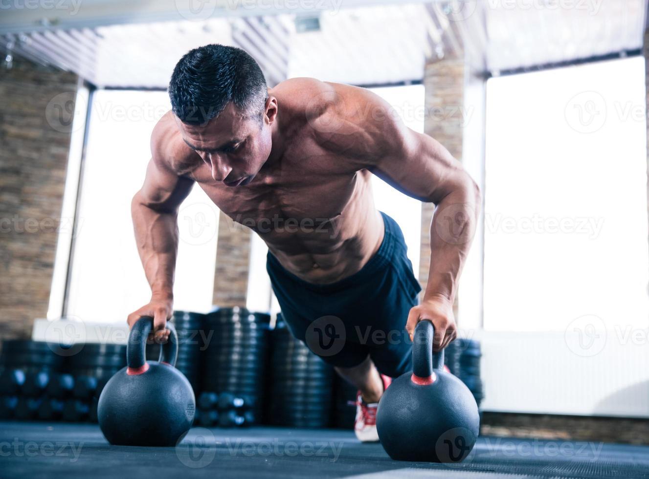 hombre musculoso haciendo flexiones en el gimnasio foto