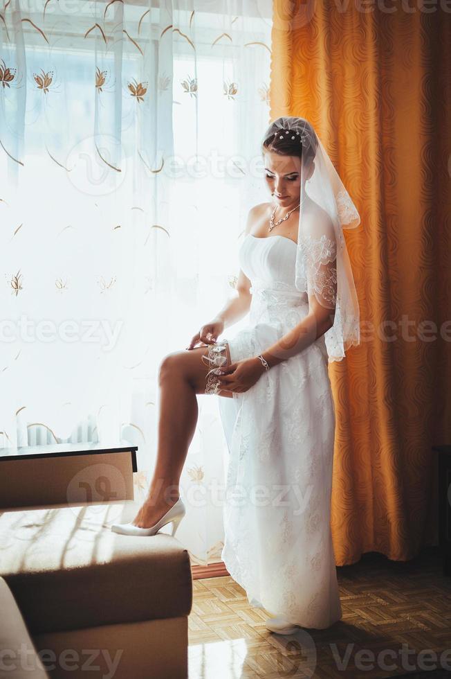 hermosa novia preparándose en vestido de novia blanco con peinado foto