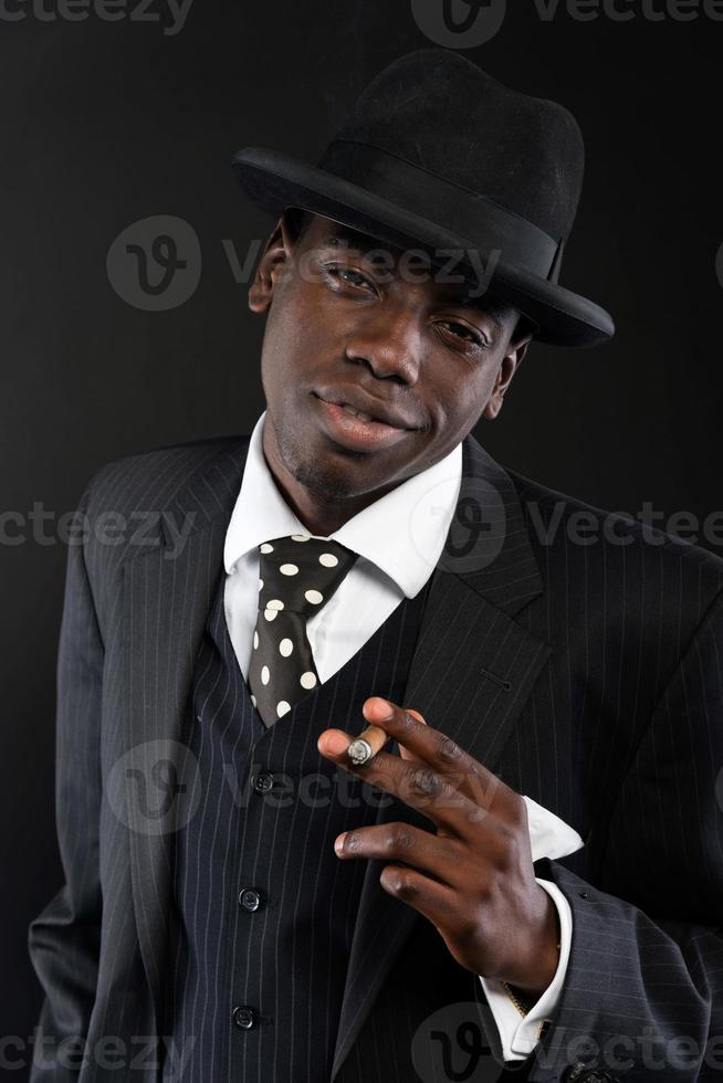 Retro african american mafia man wearing striped suit and tie. photo