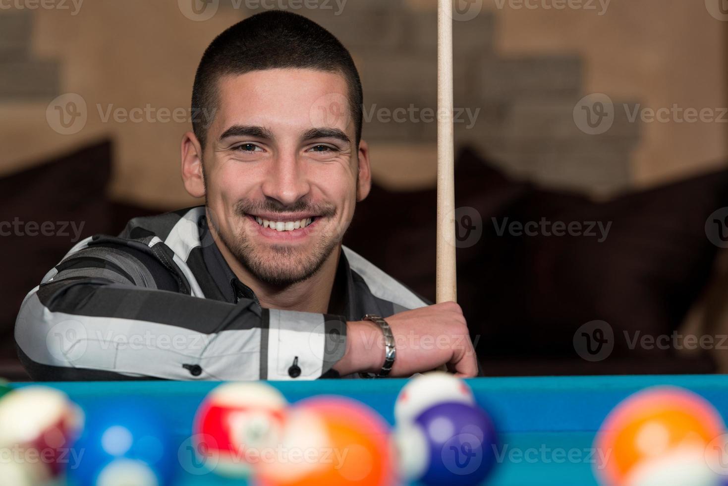 hombre feliz sonriente jugando billar foto