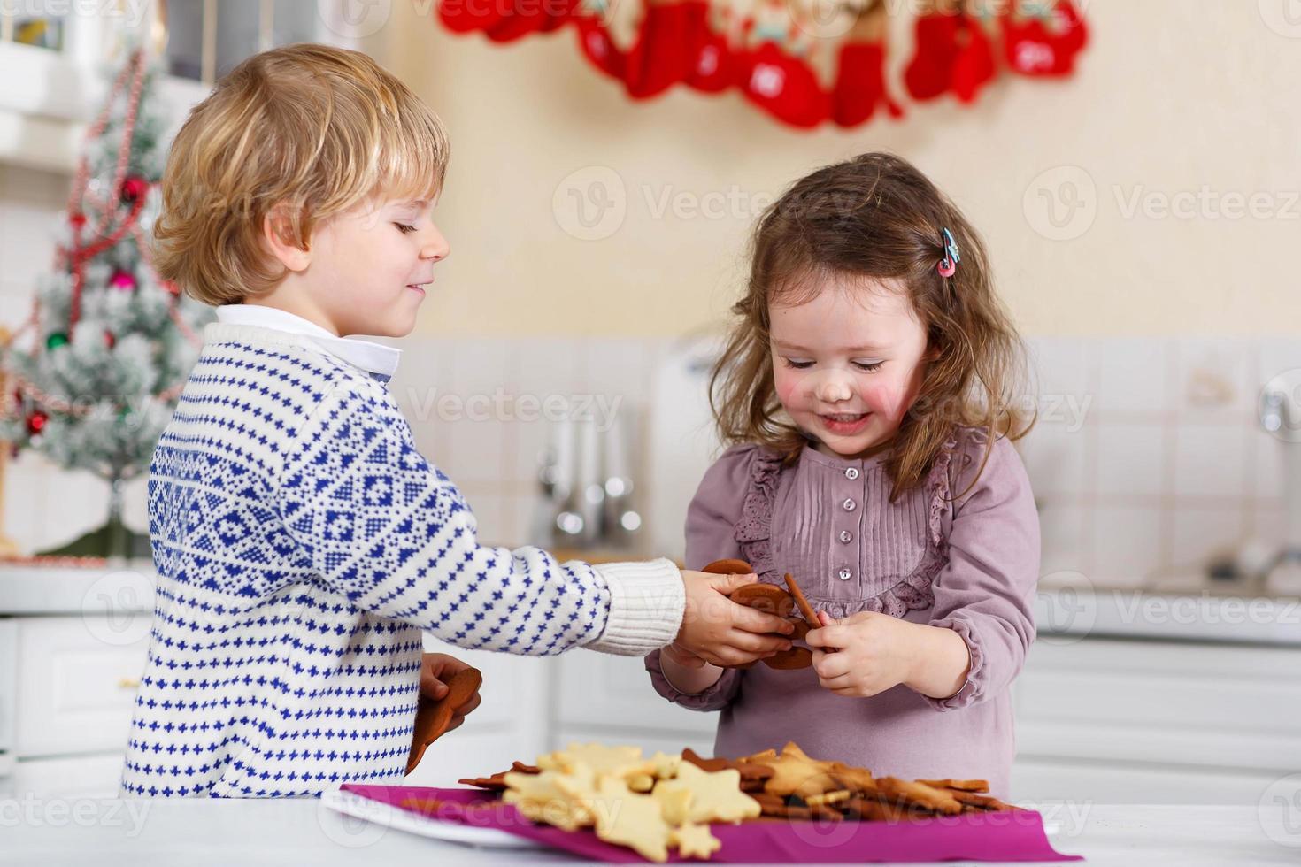 niño y niña horneando galletas de navidad en casa foto