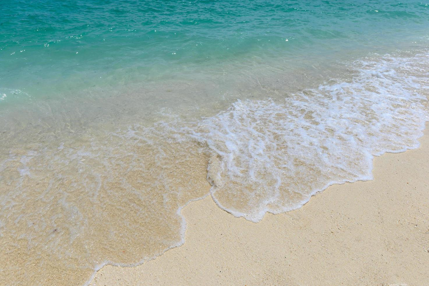 Blue waves splash on white beach photo