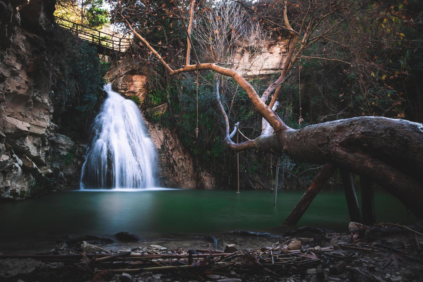 Cyprus waterfall over green waters photo