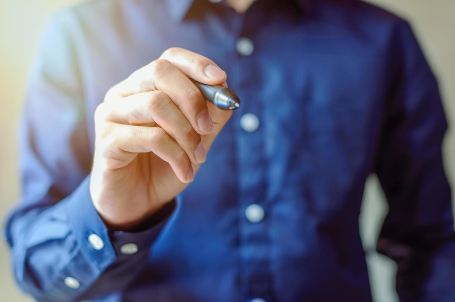 Businessman uses a pen photo