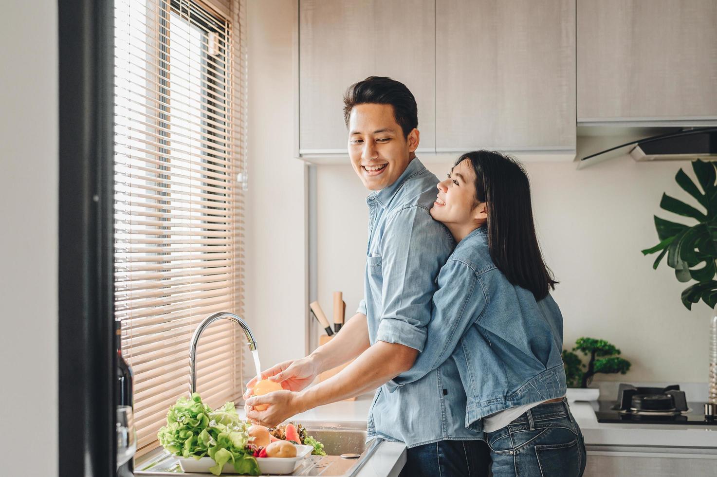 Pareja asiática lavar verduras en el fregadero de la cocina foto