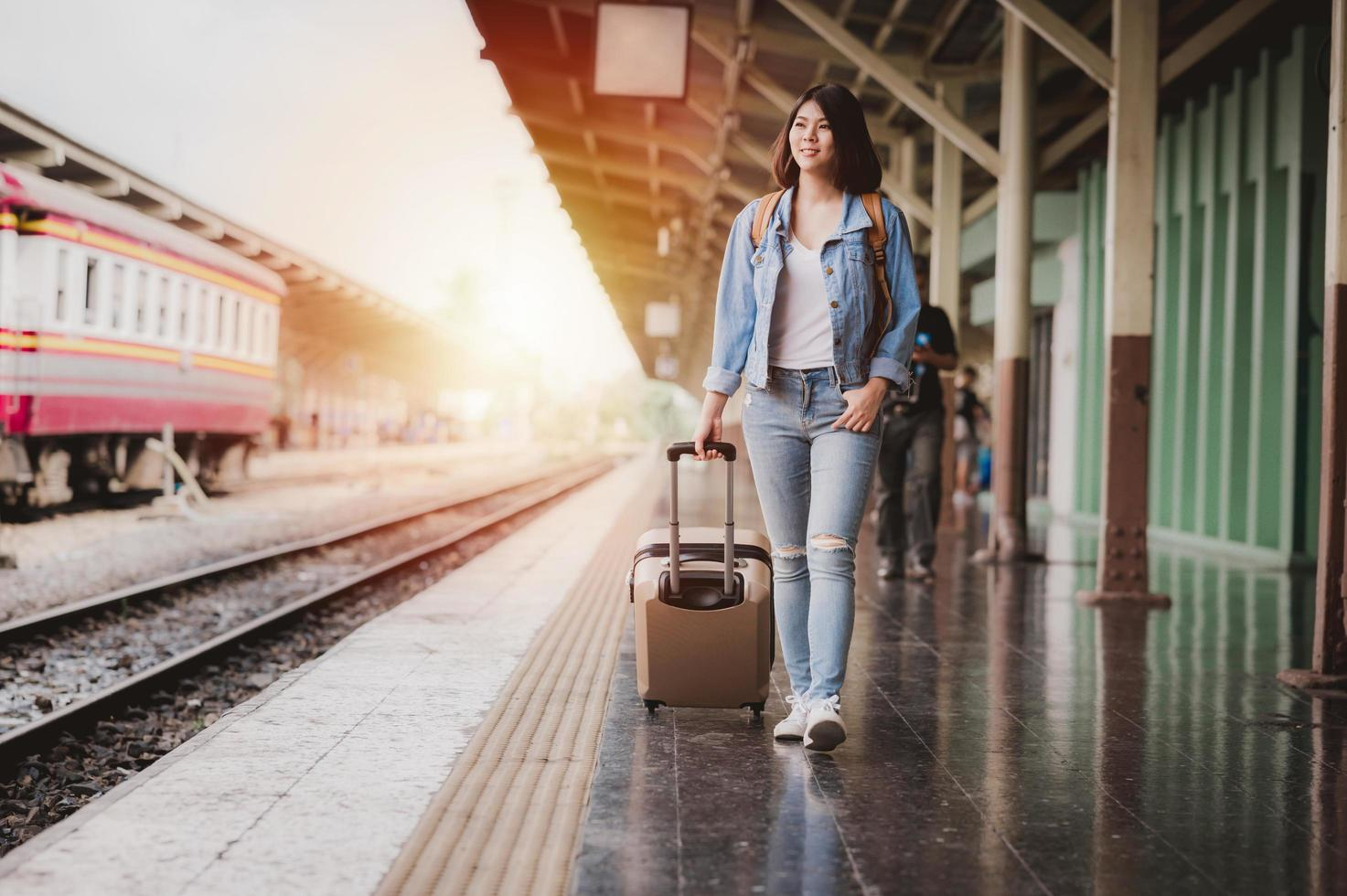 Woman with luggage at train station photo