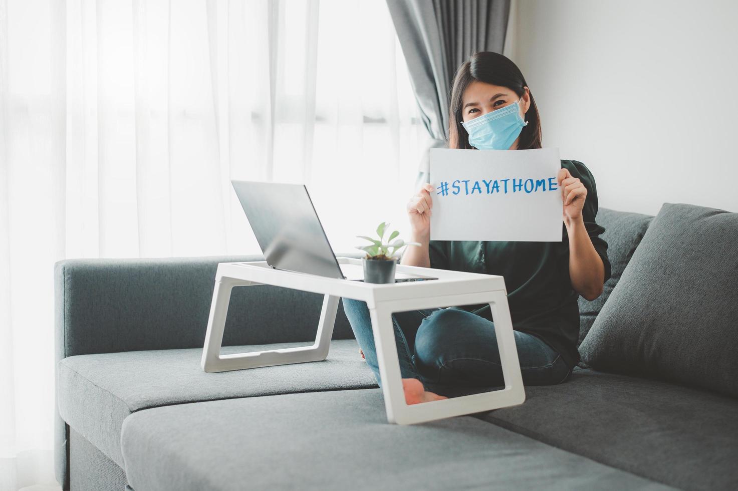mujer con mascarilla trabajando en casa foto