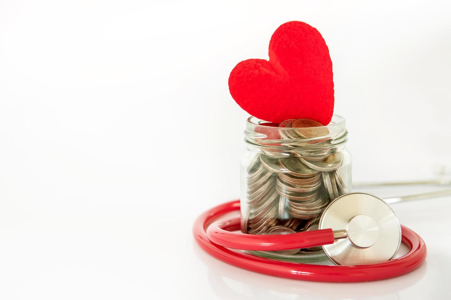 estetoscopio envuelto alrededor de un frasco de monedas con corazón foto