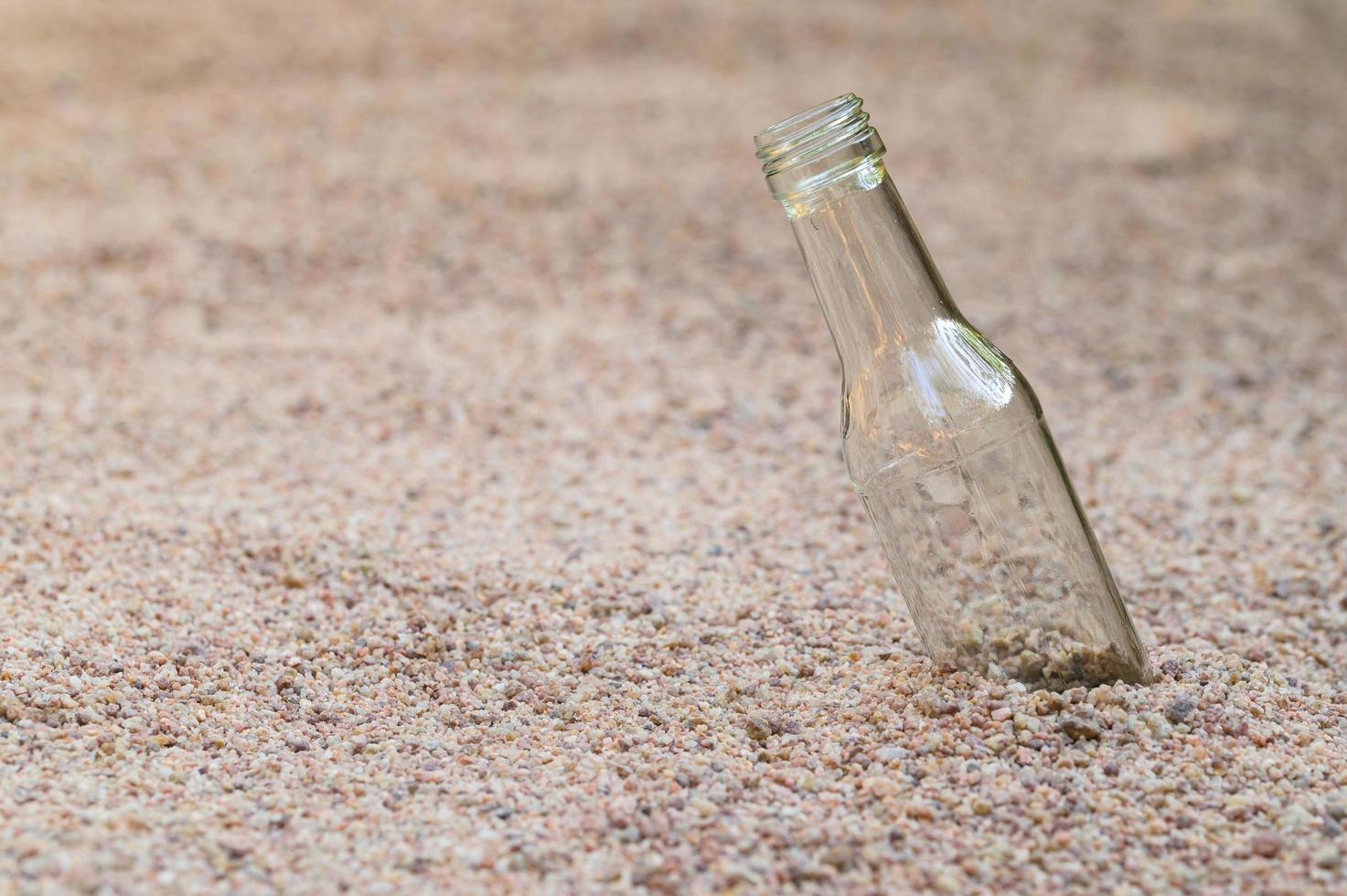 Empty glass bottle on the beach photo