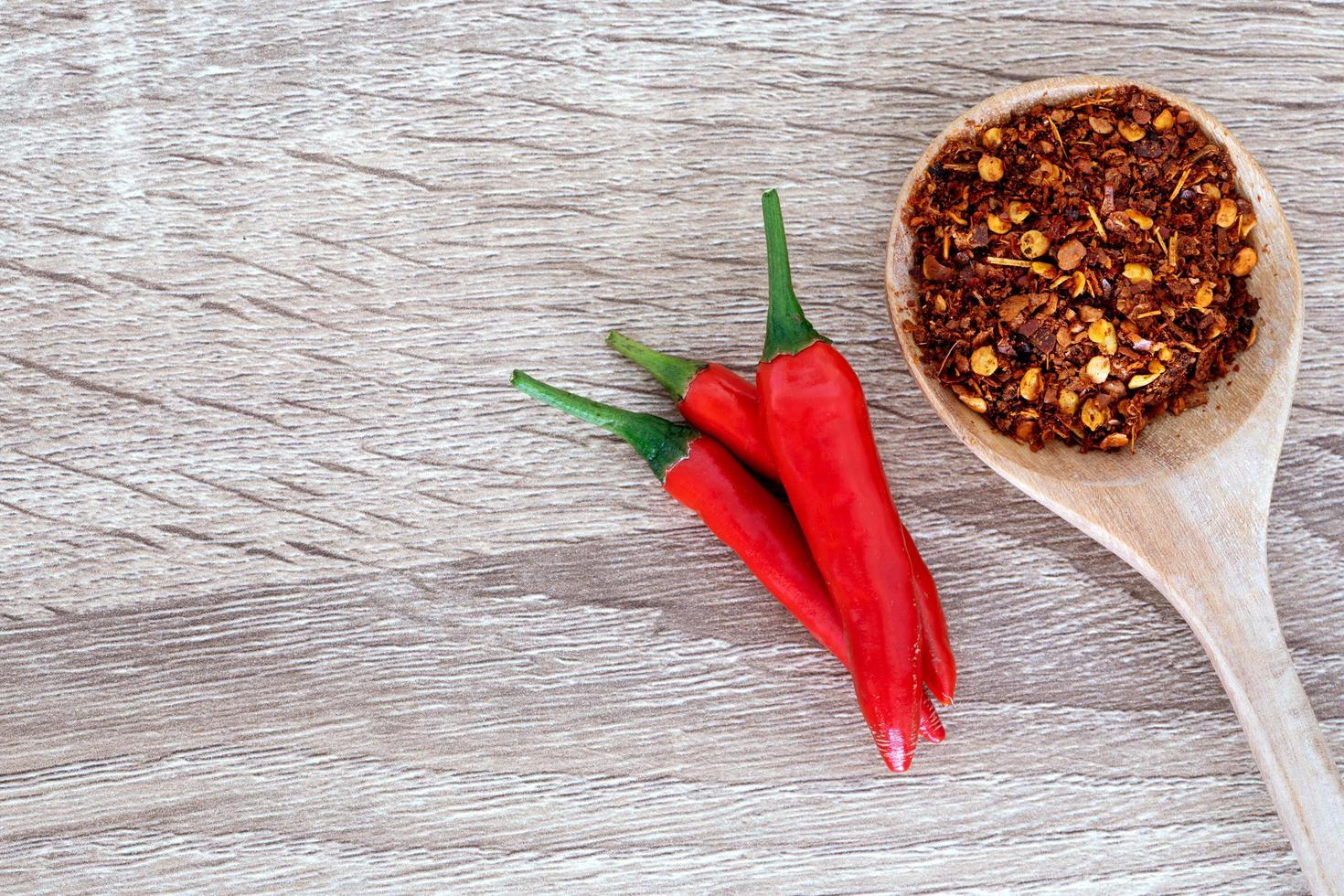 Fresh and crushed chili peppers on wooden table photo