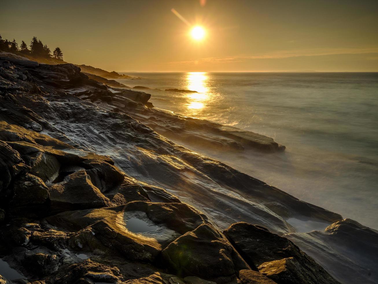 larga exposición de las olas del océano en la playa rocosa foto