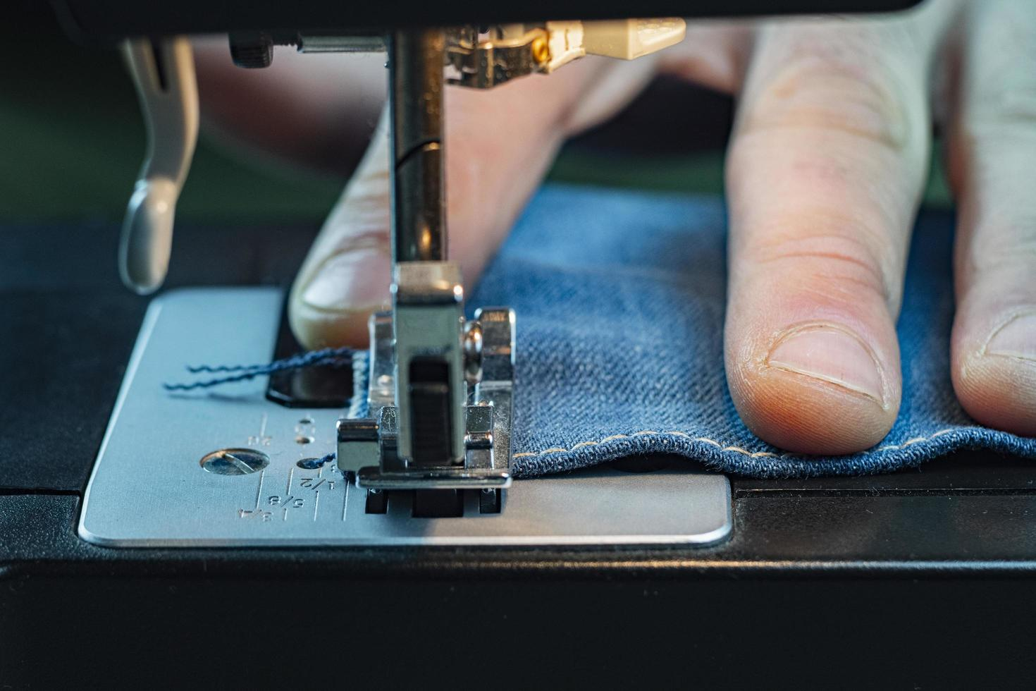 Male hand sewing denim on a sewing machine photo