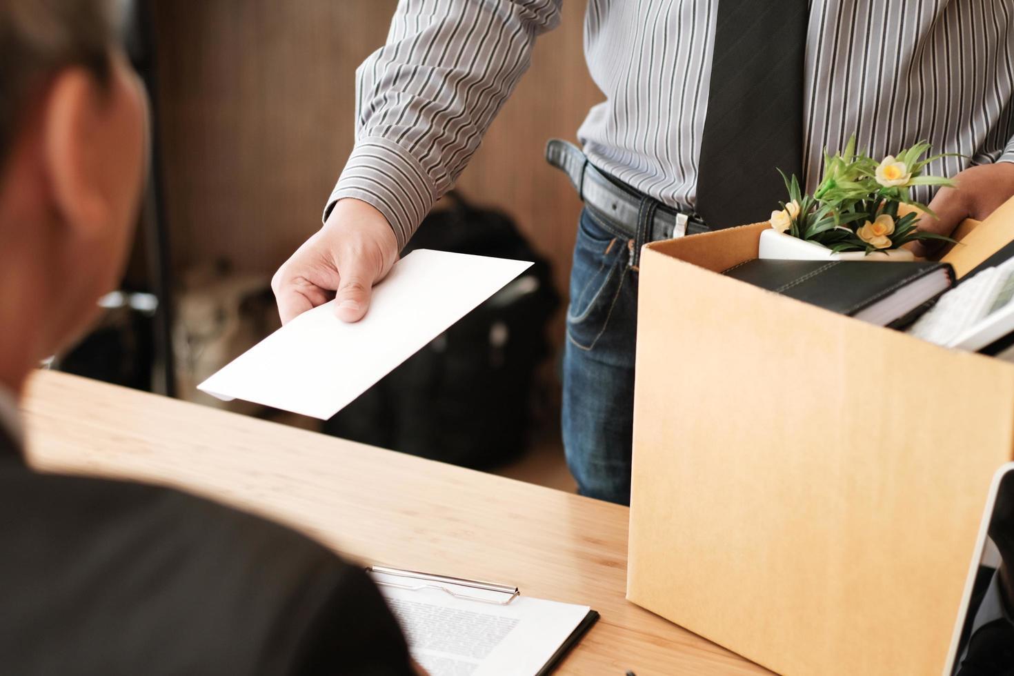 Businessman handing resignation letter to boss photo