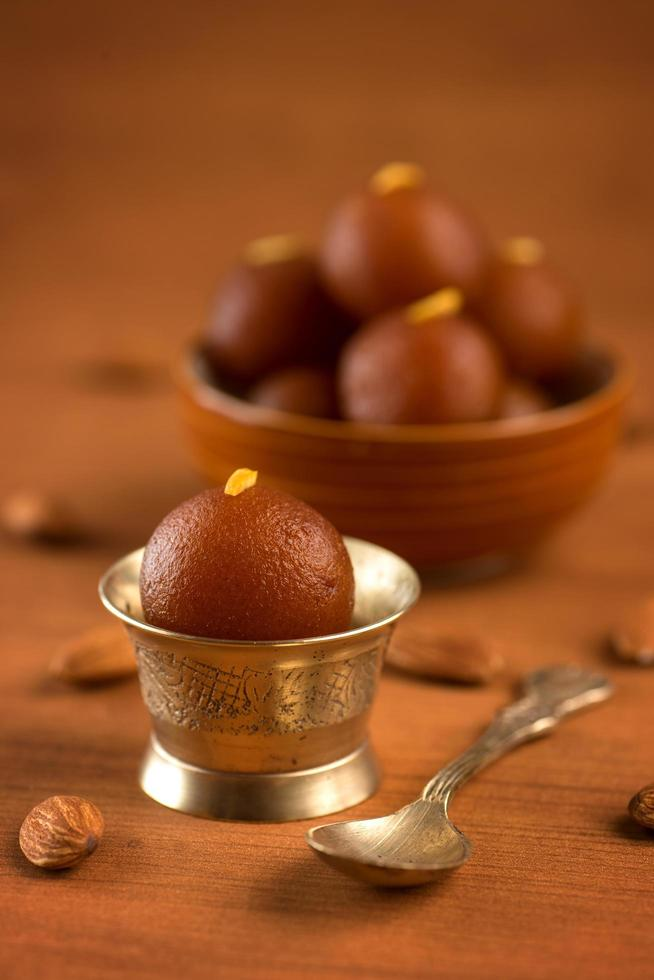 Indian Gulab Jamun dessert on wooden background photo