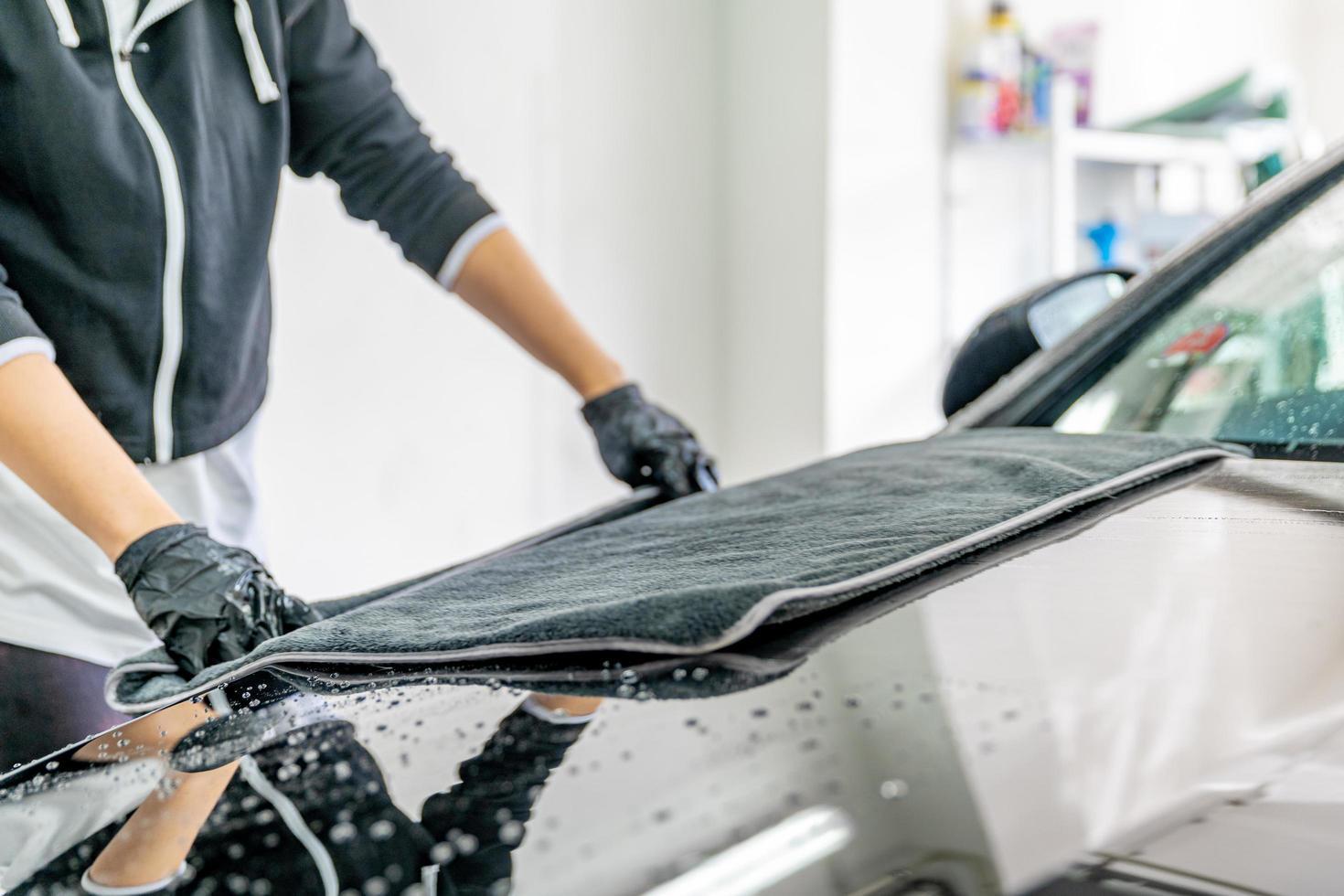 Mechanic drying off hood of car photo