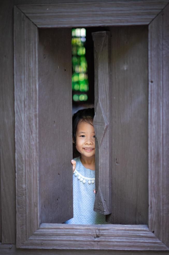 Young Asian girl peaks thru window at camera photo