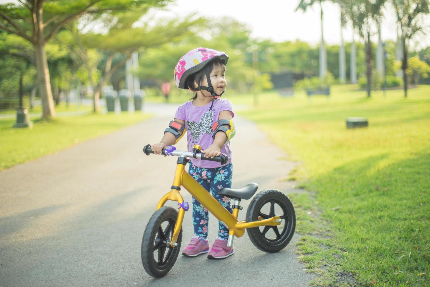 niña aprende bicicleta afuera en sendero para bicicletas foto