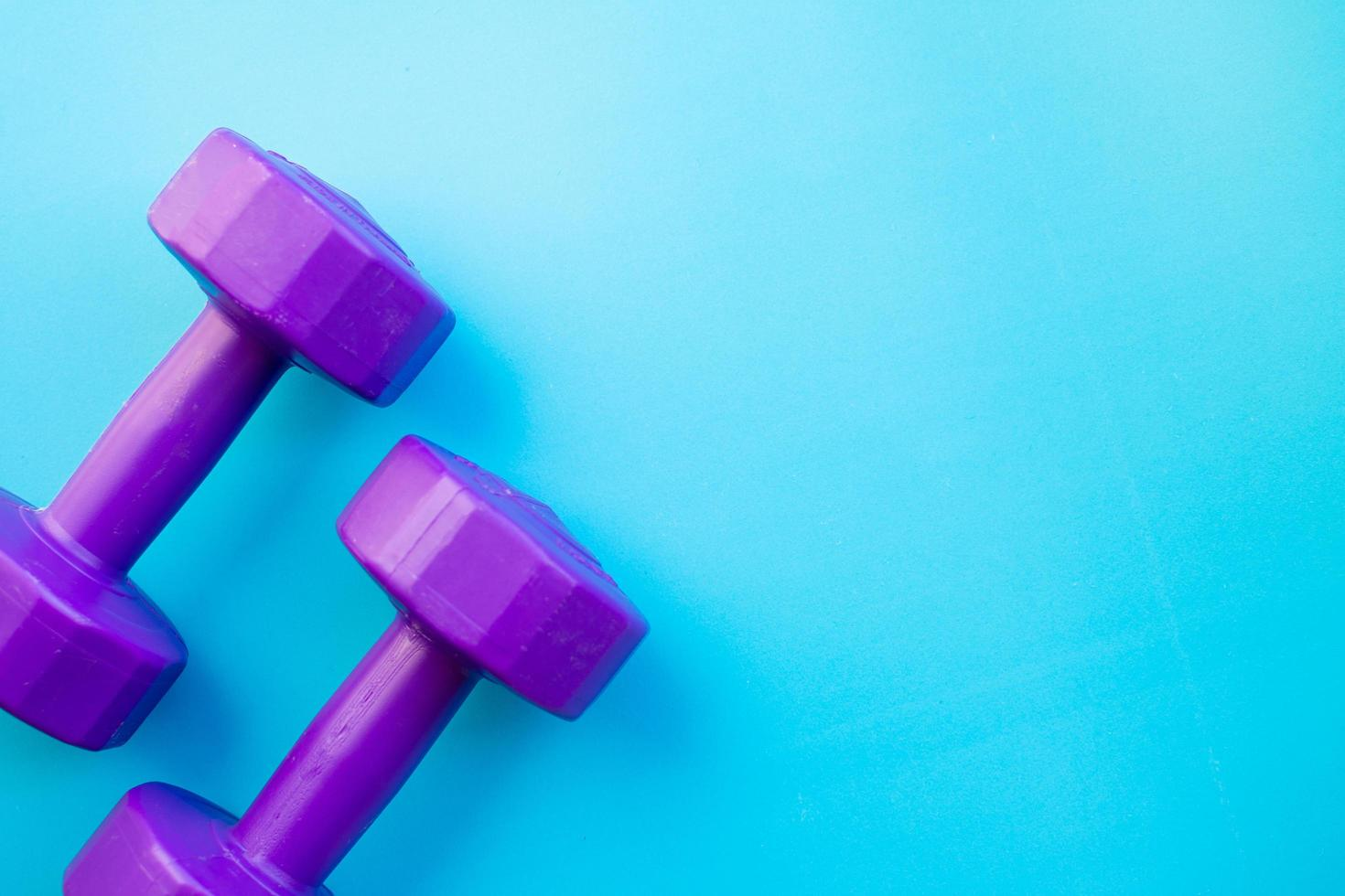 Fitness dumbbells on color background photo